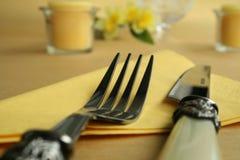 Couteau et fourchette sur la nappe jaune Photographie stock libre de droits