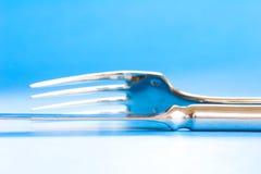 Couteau et fourchette sur le fond bleu Photographie stock