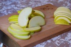 Couteau et pomme sur une planche à découper sur une table dans la cuisine Pommes de Chantecler photographie stock libre de droits