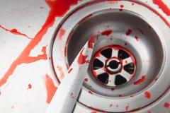 Couteau et sang dans l'évier Image libre de droits