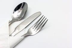 Couteau, fourchette et cuillère avec la serviette, d'isolement sur le fond blanc photos stock