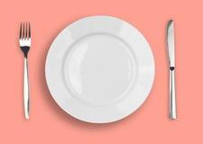 Couteau, plaque blanche et fourchette sur le fond rose Photo stock