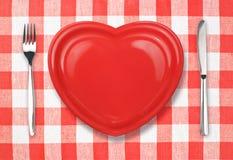 Couteau, plaque dans la forme de coeur et fourchette sur la nappe Photos libres de droits