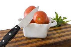 Couteau, tomates, panneau de découpage sur le blanc Images libres de droits