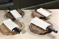 Couteaux avec des serviettes et conseils en bois sur la table de cuisine image libre de droits