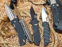 Couteaux de chasse se pliants sur la bois-laine et les cordes Photos stock
