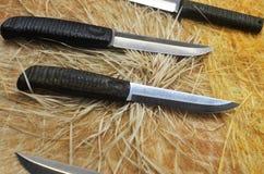 Couteaux de chasse sur un fond de bois et de foin Photographie stock