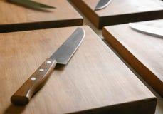Couteaux et conseils en bois sur la table de cuisine photographie stock