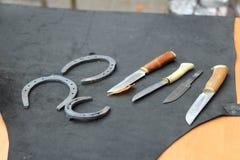 Couteaux et fers à cheval sur la table Image libre de droits