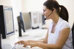 Écouteur s'usant de femme dans le sourire de salle des ordinateurs Photographie stock libre de droits