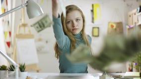 Couting kassapengar för ung nätt kvinna och kasta dem till kameran stock video