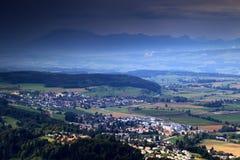 Coutryside svizzero con i villaggi, il terreno coltivabile, la foresta e le montagne Fotografia Stock