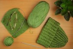 Couture, aiguilles de tricotage et crochet, chapeau de fil vert clair, fleur à la maison Photographie stock libre de droits
