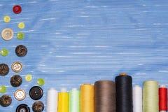 Couture et concept de mise sur pied - boutons de couture, bobines de fil et tissu Photo stock