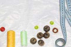 Couture et concept de mise sur pied - boutons de couture, bobines de fil et tissu Image libre de droits