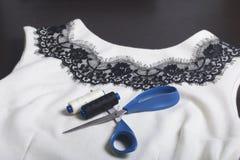 Couture et habillage Sur l'obscurité la surface est une robe blanche avec un ruban noir cousu pour la décoration Il y a des cisea Photo stock