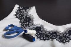 Couture et habillage Sur l'obscurité la surface est une robe blanche avec un ruban noir cousu pour la décoration Il y a des cisea Image stock