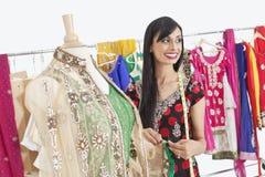Couturière féminine assez indienne semblant partie tout en travaillant à l'équipement traditionnel Photos stock