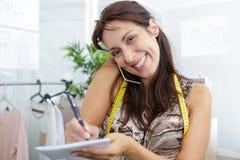 Couturière féminine prenant des notes tout en parlant au téléphone images libres de droits