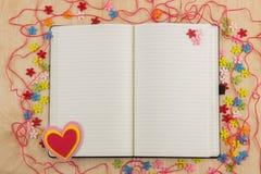 Couturière ouverte de page de carnet avec des boutons, fil, fleurs et Image stock
