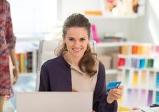 Couturier à l'aide de l'ordinateur portable avec la carte de crédit Images stock