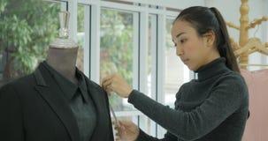 Couturier attirant travaillant à un costume dans son studio banque de vidéos