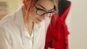 Couturier avec les modèles et les ciseaux de couture dans une usine de textiles Papier de ciseaux de concepteur banque de vidéos