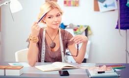 Couturier de jeune femme travaillant au studio photos libres de droits