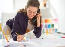 Couturier de sourire dans le téléphone parlant de bureau Image stock