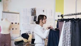 Couturier féminin attirant prenant le pantalon du support d'habillement avec les vêtements élégants à la mode banque de vidéos