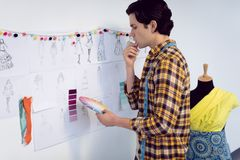 Couturier masculin regardant l'échantillon de couleur photographie stock