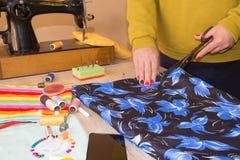 Couturier, tailleur de femme posant sur son lieu de travail avec le tissu coupé, l'espace libre sur la table de travail en bois Photos stock
