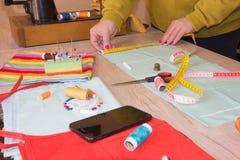 Couturier, tailleur de femme posant sur son lieu de travail avec le tissu coupé, l'espace libre sur la table de travail en bois Photo stock