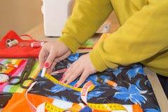 Couturier, tailleur de femme posant sur son lieu de travail avec le tissu coupé, l'espace libre sur la table de travail en bois Images stock