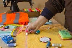 Couturier, tailleur de femme posant sur son lieu de travail avec le tissu coupé, l'espace libre sur la table de travail en bois Photographie stock