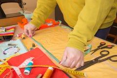 Couturier, tailleur de femme posant sur son lieu de travail avec le tissu coupé, l'espace libre sur le mur en bois Photo libre de droits