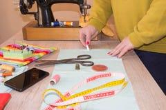 Couturier, tailleur de femme posant sur son lieu de travail avec le tissu coupé, l'espace libre sur le mur en bois Photos libres de droits