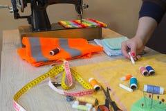 Couturier, tailleur de femme posant sur son lieu de travail avec le tissu coupé, l'espace libre sur le mur en bois Photos stock