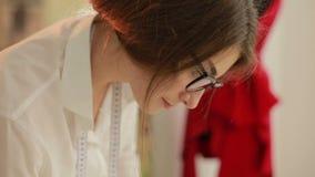 Couturier travaillant à la table Main de modèle femelle de dessin de tailleur au papier dans son studio tailleur féminin avec le  banque de vidéos