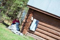 Couturière mûre s'asseyant à l'ombre et travaillant près de la maison Photographie stock