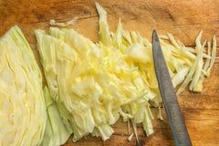 A couve branca é cortada para a salada Localizado em uma placa de madeira ao lado da faca imagem de stock
