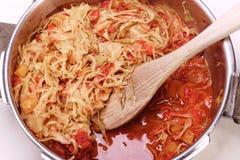 Couve e pimentas vermelhas no fogão de pressão Foto de Stock