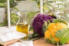 Couve-flor-brilhante roxo e amarelo, costeleta, azeite Fotografia de Stock Royalty Free