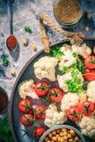 A couve-flor do prato de vegetariano dos ingredientes cozeu tomates dos grãos-de-bico fotografia de stock