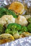 A couve-flor e os brócolis com limão, especiarias e tomilho cozeram na folha no forno imagem de stock royalty free
