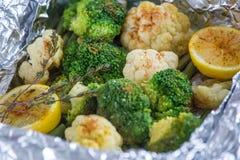 A couve-flor e os brócolis com limão, especiarias e tomilho cozeram na folha no forno fotos de stock royalty free
