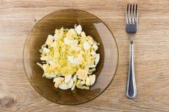 Couve fritada com os ovos na placa e na forquilha marrons Imagem de Stock