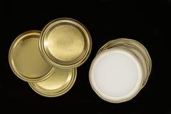 Couvercles d'or de pot d'isolement sur le fond noir photos stock