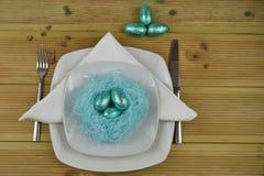 Couvert de table de Pâques dans le blanc avec le nid bleu fait main de couleur et les oeufs de chocolat brillants bleus Photos libres de droits