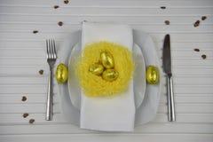 Couvert de table de Pâques dans le blanc avec le nid fait main jaune et les oeufs d'or de couleur Image stock